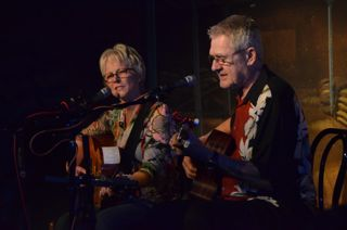 photo of Tracy Newman playing guitar beside Art Podell