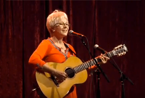 photo of Tracy Newman Singing On Stage, playing acoustic guitar