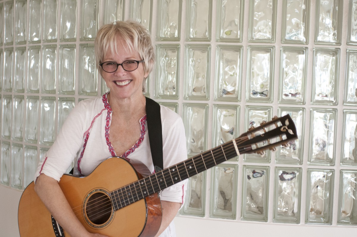 tracy-newman-smiling-with-guitar-and-glass-wall-behind