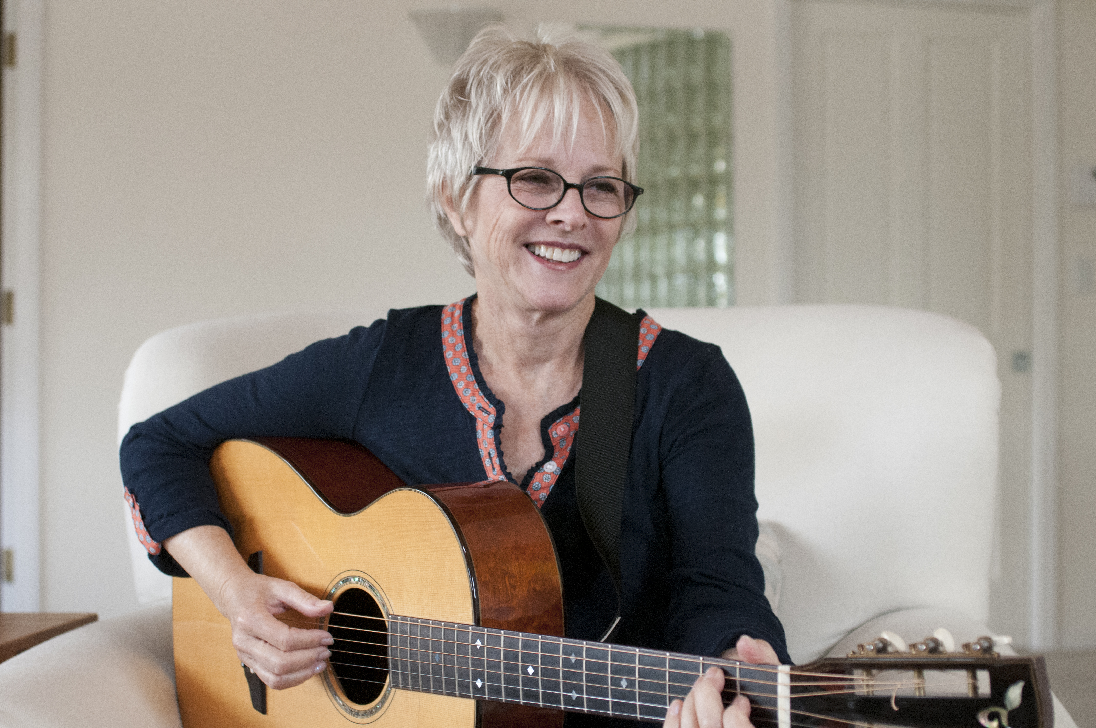 tracy-newman-smiling-to-the-side-with-guitar