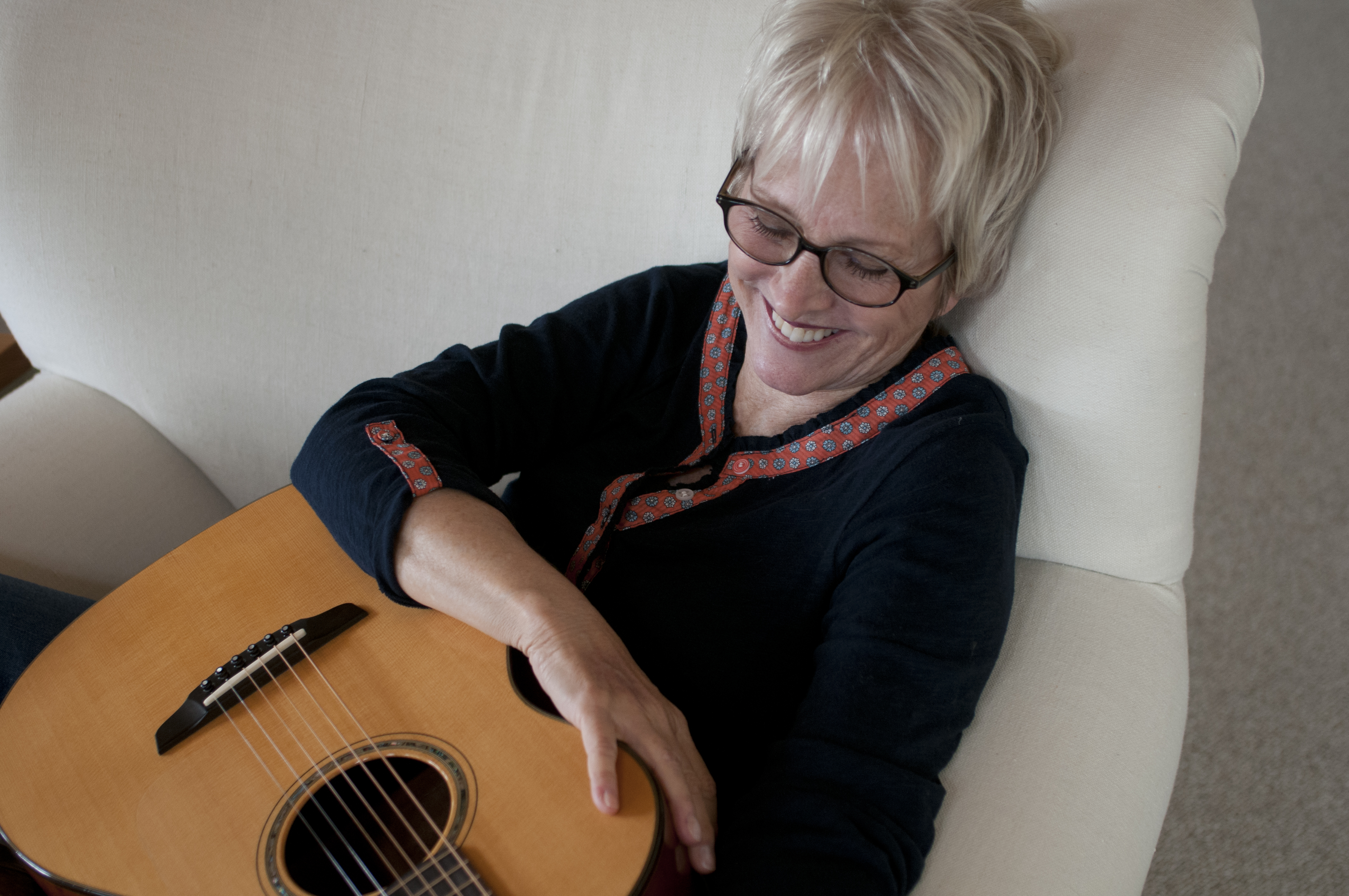 tracy-newman-smiling-from-above-with-guitar